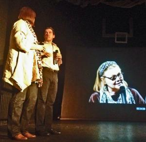 UI Director Carol MacVey (on screen) with MXAT host Adam Muskin and Russian playwright Ksenia Dragunskaya on stage in Moscow.