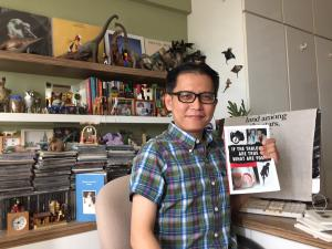 Yeow Kai Chai at his desk, holding a collection of poetry from Matthea Harvey, purchased after her reading at Prairie Lights.