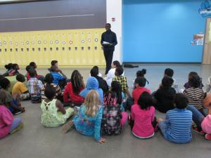 (Click to Enlarge) Oscar Ranzo (Uganda) reading to school children in Des Moines, Iowa.