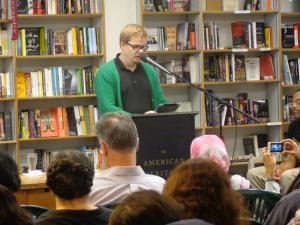 (Click to Enlarge) Poet, critic, and scholar Teemu Manninen at the podium in Prairie Lights Bookstore.