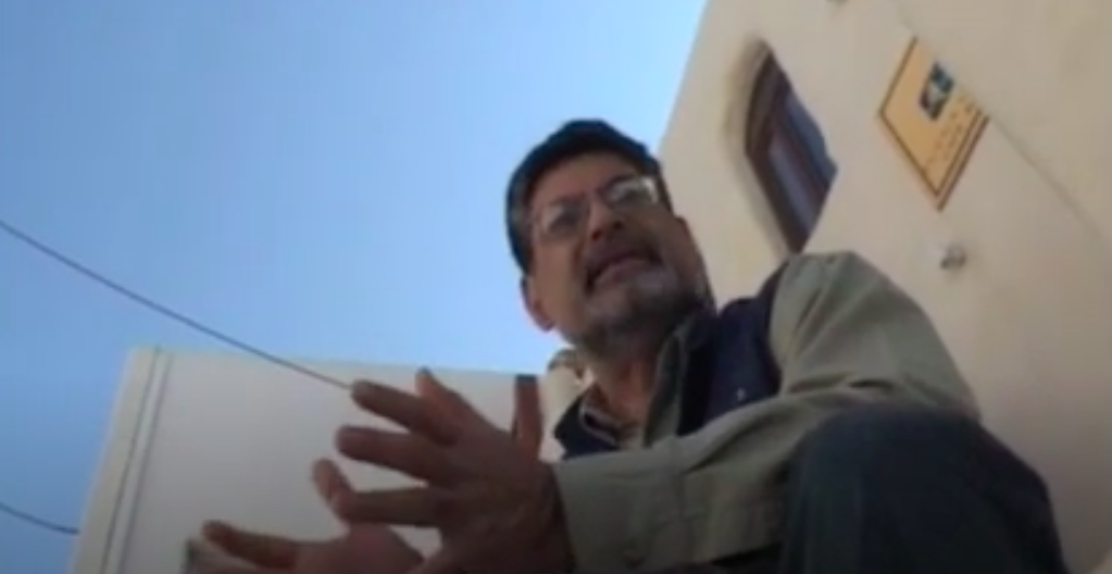 A man wearing glasses speaks in front of a building, the camera looks up from below