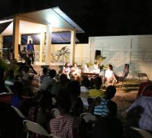 A public reading held at night in the court yard of a community art center.jpg