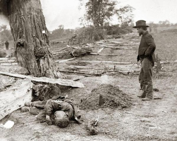 Alexander Gardner photograph of a Union soldier at the grave of another Union soldier, with a Confederate soldier's body left unattended. Antietam Battlefield. Source: National Park Service.